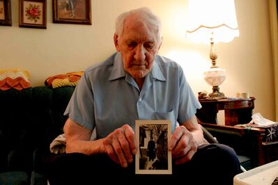 Hansell holds up a 1936 photo of himself standing in the front yard of his childhood home.
