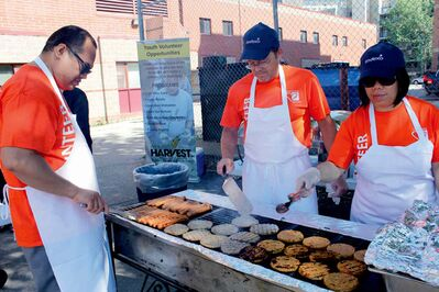 Geoff Gementiza (left), Grant McFarlane and Arlene Bugtong are seen cooking burgers and hot dogs.