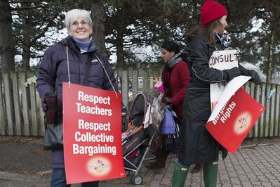 A woman pushes a stroller past striking teachers as they stand on a picket line in Toronto on Tuesday, December 18, 2012. Elementary school teachers are staging a one day action as they protest the introduction of Bill 115. THE CANADIAN PRESS/Chris Young