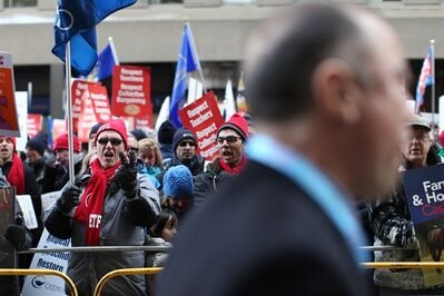 An Ontario Liberal Party delegate is verbally abused as protesters gather outside Toronto's Maple Leaf Gardens on Saturday, January 26, 2013 while the party gathers to vote for a new provincial Leader and in turn a new premier of Ontario. THE CANADIAN PRESS/Chris Young