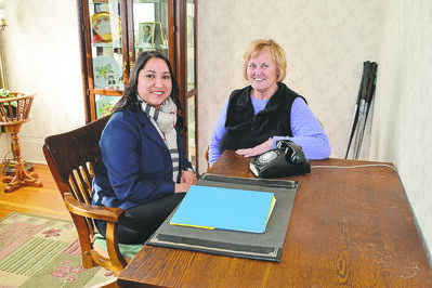 Coun. Devi Sharma and Edna Krosney, president of McBeth House Centre, sit at Alexander McBeath's original desk. In 2013, Krosney was able to recover the original desk that had been sold in the 1980s.