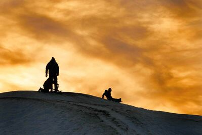"A young family slides down ""Garbage Hill"" at Westview Park amid a setting sun Saturday, December 21, 2013."