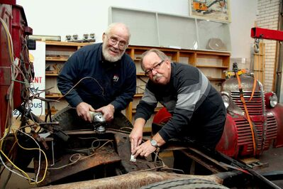 Leon St. Onge and Dave Wiebe sand the frame of St. Vital No.1, a 1939 Fargo pumper truck, at the St. Vital Museum.