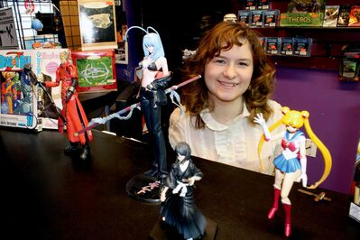 Tabitha McLelland poses with some of the figurines sold at Raven Toys & Collectibles. She is the executive director of Wonderland Anime Festival.