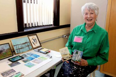 Joan Hibbert holds up some of her wax art.
