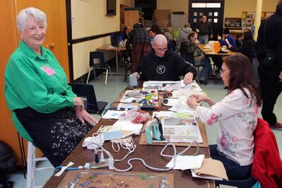 Joan Hibbert (left) sits at her table at the Oak Table while Michael Turner and Martha Chief make some artwork.