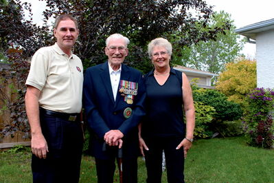 Hong Kong Veterans Commemorative Association (HKVCA) National Convention chairperson Dennis Bell, veteran George Peterson, and HKVCA national president Carol Hadley are shown at Peterson's Windsor Park home.