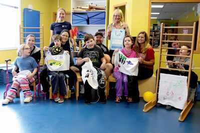 Margy Nelson (back right), executive director at the Movement Centre of Manitoba, with some of the staff and clients at the facility. Some of the younger clients are taking part in their own Olympic Games and are showing off their individual flags.