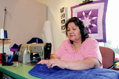 Viola sews together another Star Blanket at Neechi Commons, with a finished blanket hanging behind her.