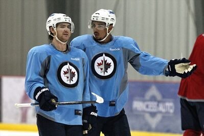 Evander Kane (right)) and Jim Slater discuss a play during practice at the MTS Iceplex Thursday . They will be on the ice outdoors at The Forks Sunday afternoon at 1:30 p.m.
