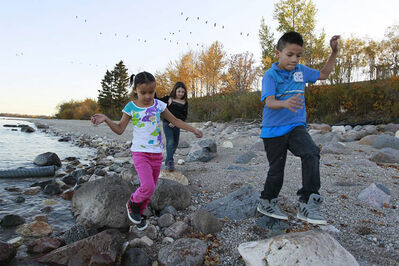 Anika Wetherill (centre), Kenisty St Clair (background) and Zach Cruly from Little Saskatchewan First Nation play on the shore of Lake Winnipeg at Misty Lake Lodge in Gimlie. The community has been evacuated due to flooding since May of 2011.