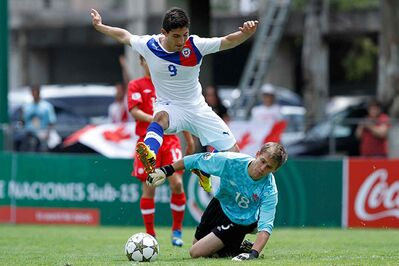 Alic Rasmussen (right) dives at the feet of a Chilean opponent while in action for Canada against Chile in Mexico in August 2013.