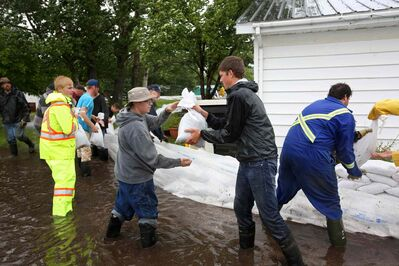 Volunteers help build a sandbag dike around a home in Reston on Sunday.