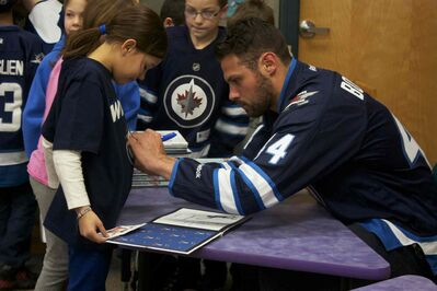 Winnipeg Jets defenceman Zach Bogosian signs a young fan's shirt at Princess Margaret School on Feb. 25. Bogosian and centre Mark Scheifele attended the I Love to Read Month event through the team's Reading Takes Flight program.
