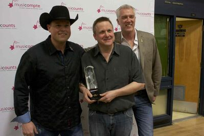 River East Collegiate music teacher Jeff Kula (centre), country artist Gord Bamford (left), and MusiCounts director Allan Reid (right) are shown. Kula won the MusiCounts teacher of the year award on March 26.