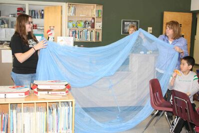 Laura Bailey from the the University of Manitoba's Spread the Net Student Challenge and Sherwood School principal Theresa Hunt show off a malaria net to some Sherwood students.