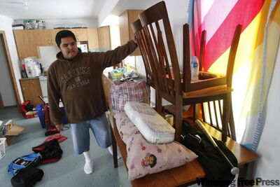 Roseau River resident Raymond Alexander raises his belongings to protect them from flooding.