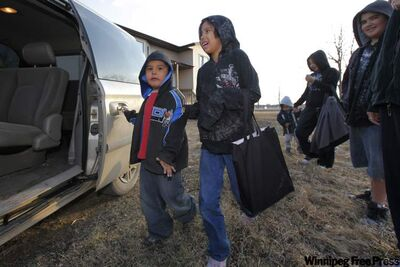Treyton Thomas, Lexus Atkinson and their relatives load a van during an evacuation of 200 people in Roseau River First Nation Saturday.