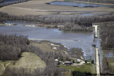An aerial view of water flowing from a deliberate breach in the dike holding back the Assiniboine River at Hoop and Holler Bend Saturday afternoon. The breach was made Saturday morning.