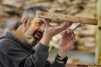 Gilbert pays close attention to varnishing wood for use in table and- chair sets and miniature barns.
