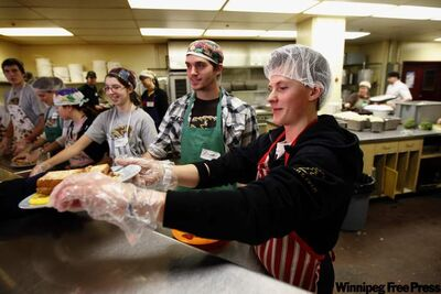 Bison track athletes Zac Clapa, Elliott Cooke and Megan Moorehouse (from right) serve breakfast at the Siloam Mission. Over 100 Bison athletes chipped in as servers this year.