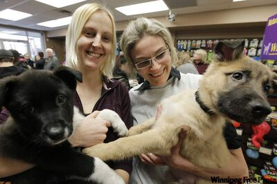 Becky Nordquist (left) and Lisa Rasmussen cuddle Brooklyn and Bishop at Manitoba Mutts.