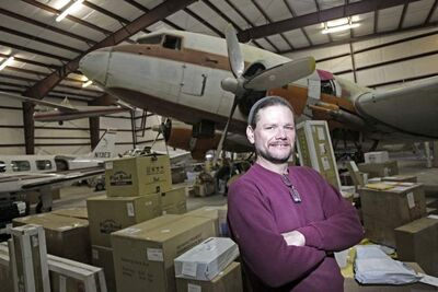 Pembina Parcel employee David Lavaty in an airport hangar that doubles as the company's warehouse.