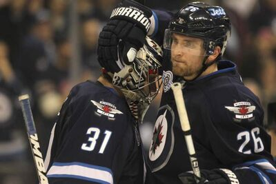 Winnipeg Jets goalie Ondrej Pavelec gets congratulated by his fellow player Blake Wheeler, No. 26, after winning against Boston 4 - 2 Friday.