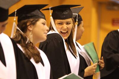 Rayanna Chartrand (left) smiles and giggles with Kayla Prince (right) during a ceremony in June honouring graduates of the adult-education program at the Turtle Mountain Rec Centre.