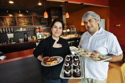 Ronak Arjomandi, left, with the grilled chicken cheddar melt and the Chocolate Dome and Peyman Esfehani, right, with the imperial cookies at Cottage Bakery.