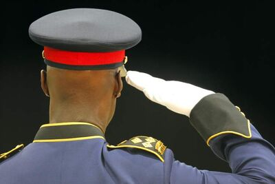 Police Chief Devon Clunis salutes police academy grads last year. A draft of a review of police operations proposes deep cuts.
