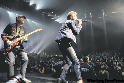 BORIS.MINKEVICH@FREEPRESS.MB.CA  Coldplay�s lead singer, Chris Martin, belts it out at the MTS Centre as Jonny Buckland plays guitar.