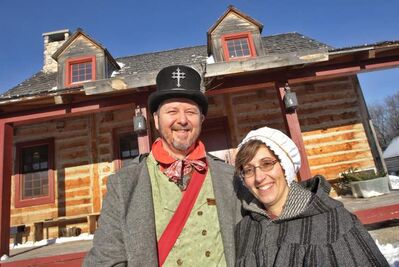 Members of the official Festival du Voyageur family, Daniel St. Vincent and Jocelyne Gagnon, outside the main building in Fort Gibraltar.