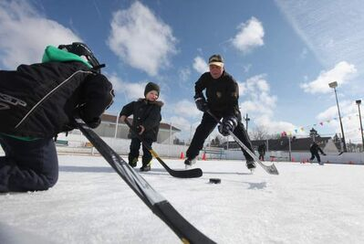 Roblin Park Community Club icemaker Marcy Beaucage plays a little hockey with his grandson Kiedis Chudyk Saturday morning.