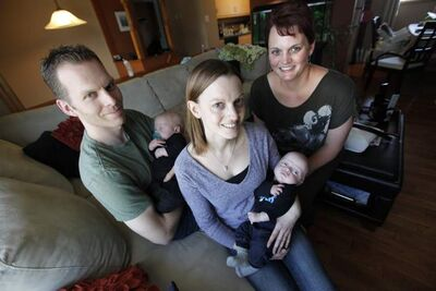 Mike Olson and his wife, Lisa Seel, hold their sons, Keenan and Kai, respectively. At right, Lisa's sister, Averill Stephenson.