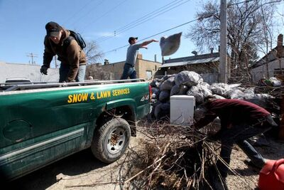 A SSCOPE crew empties a truck full of leaves, brush and supplies at the Arlington Street depot at the end of a spring-cleaning workday.