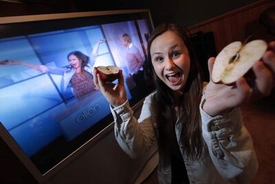 Kirsten Kettler, back home Monday watching her taped TV appearance, demonstrates her talent with apples.