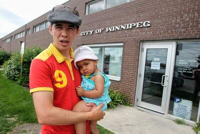 Robert-Falcon Ouellette with his daughter Abigaelle, 15 months, made the trip to the Winnipeg Insect Control Branch on Waverly Street to register for the buffer zone around his property.