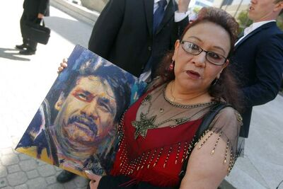 Esther Grant, older sister of the late Brian Sinclair, holds a painting by artist Gord Hagman of her brother outside of the courthouse Tuesday.