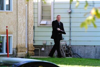 A Winnipeg police detective surveys the scene at an Essex Avenue home Sunday morning after a fatal shooting.