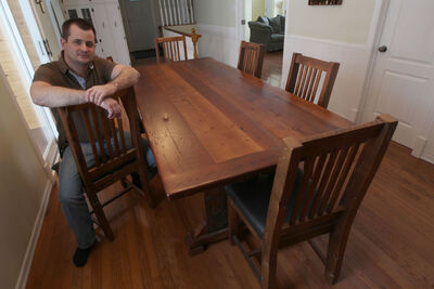 Wyton shows a dining room set his Morden company has made from wood from former barns.