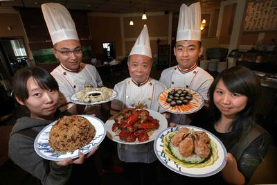 From left, Lulu Zhai, Song Ni, chef Peter Ho, Yi Yang and Summer Bai  hold, respectively, sticky rice,  dumplings, lobster platter, shrimp rolls and cuttle fish, and crab balls.