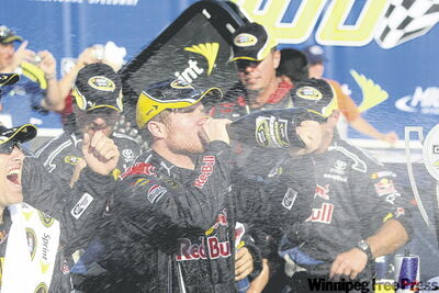 Brian Vickers swigs champagne in the winner's circle after the NASCAR Carfax 400 Sprint Cup Series race last Sunday in Michigan.