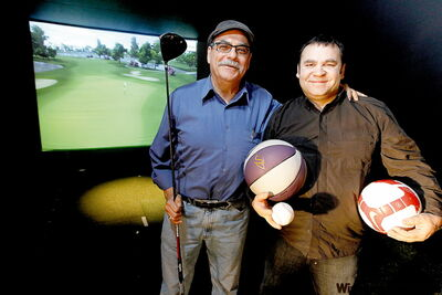 Co-owners Bernie Cheater and Jack Salvaggio in front of one of the giant golf simulators in 4Play Sportsbar and Entertainment Zone.