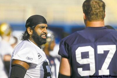 Bombers centre Obby Khan, chats with defensive lineman Doug Brown during a recent practice.