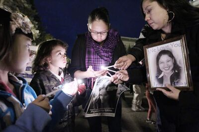 Elissa Gabriel (centre) lights candles for Mary Catcheway (right)), the sister of Jennifer Catcheway, and others at a vigil for murdered and missing women in Winnipeg in October 2011.
