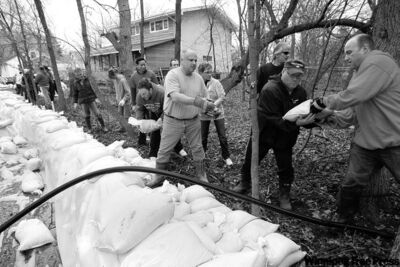 KEN GIGLIOTTI / WINNIPEG FREE PRESS Volunteers pile sandbags on a dike protecting homes in south Headingley from the rising Assiniboine River Tuesday.
