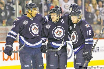 Jets (from left) Evander Kane, Tobias Enstrom and Bryan Little celebrate a goal against the Sabres in the second period Thursday. The team clicks off the ice also.
