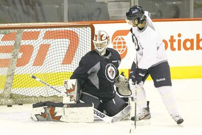Mike Deal / Winnipeg Free PressWinnipeg Jets forward Jim Slater goes to the net in front of goaltender Chris Mason during a practice at the MTS Centre on Tuesday.