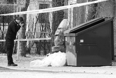 Winnipeg police investigate scene at the back of the 700 block of Notre Dame Avenue at Toronto Street last March.